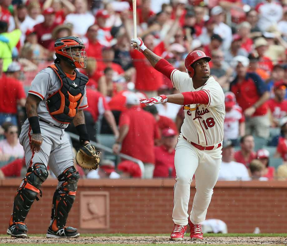 Oscar Taveras and Giants catcher Hector Sanchez have their eyes focused on the flight of Taveras' first big-league homer. Photo: Chris Lee, Associated Press