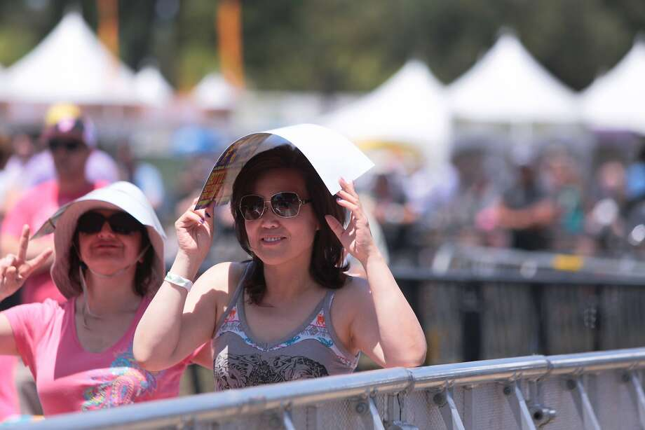 Two ladies shade themselves from the sun at the Toshiba Stage during Cracker's performance at the 2014 Bottlerock Napa Valley music, food and wine festival on Saturday, May 31, 2014 in Napa, Calif. Photo: Kevin N. Hume, The Chronicle