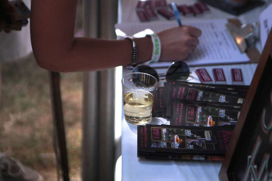 A woman leaves her wine and sunglasses on a table as she signs a mailing list at the 2014 Bottlerock Napa Valley music, food and wine festival on Saturday, May 31, 2014 in Napa, Calif. Photo: Kevin N. Hume, The Chronicle