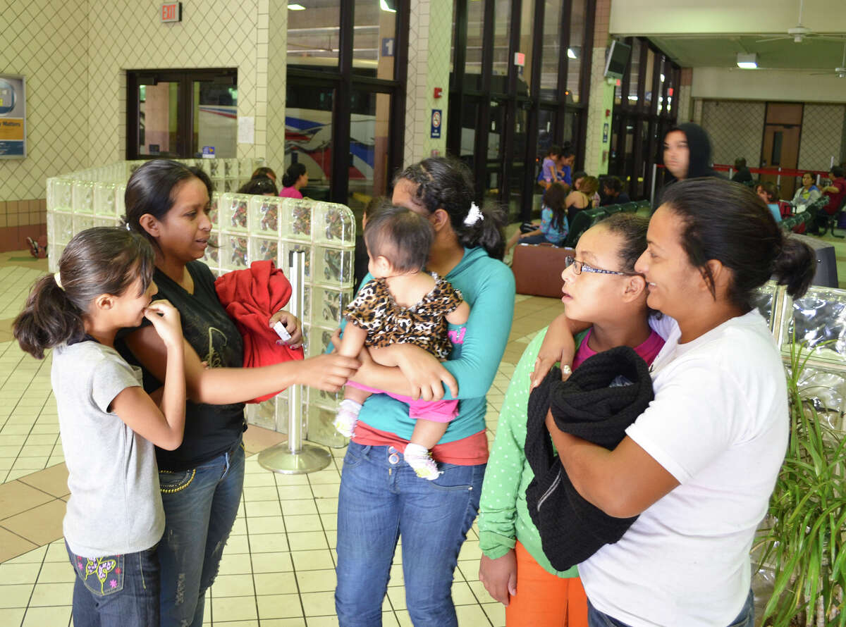 Guatemalan immigrant Flor Garcia, 34, on left in black, talks with other immigrants at the Greyhound bus station in Laredo. The women and their children were caught crossing the border illegally in the Rio Grande Valley, bused to Laredo for processing, then dropped off by U.S. officials at the bus station.