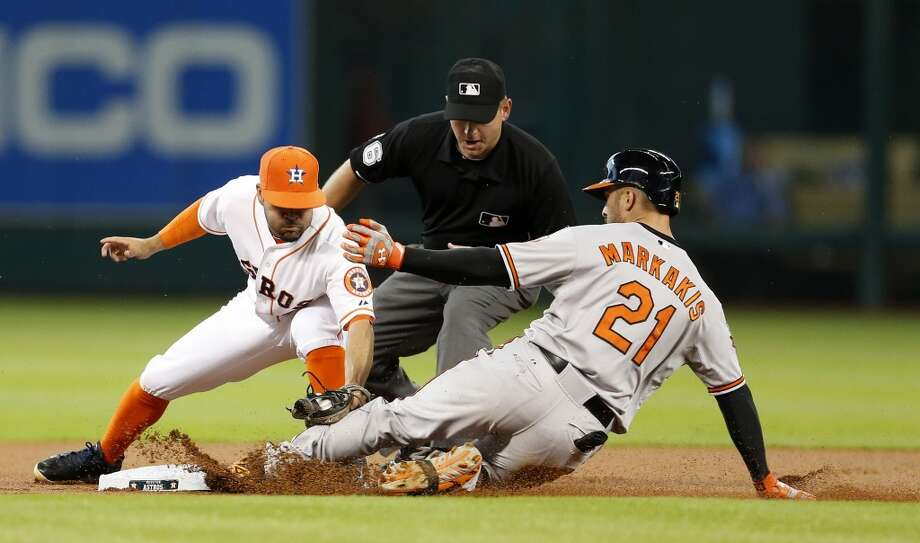 Astros second baseman Jose Altuve (27) tries to get the tag on Baltimore Orioles right fielder Nick Markakis (21) at second as he slides in on his double during the first inning. Photo: Karen Warren, Houston Chronicle