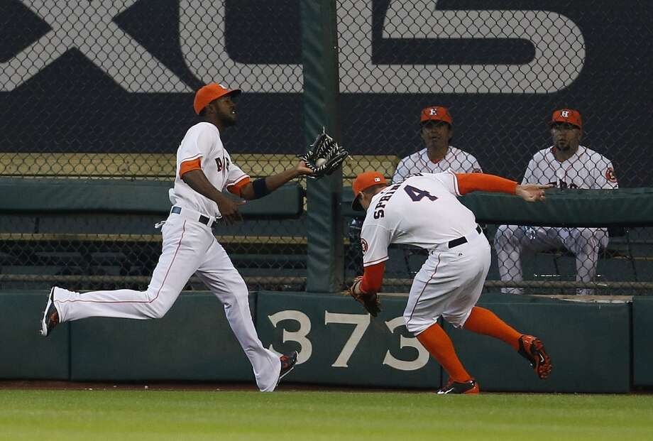 Astros center fielder Dexter Fowler (21) catches a sacrifice fly hit by Baltimore Orioles left fielder Nelson Cruz (23) as right fielder George Springer (4) assists during the first inning. Photo: Karen Warren, Houston Chronicle