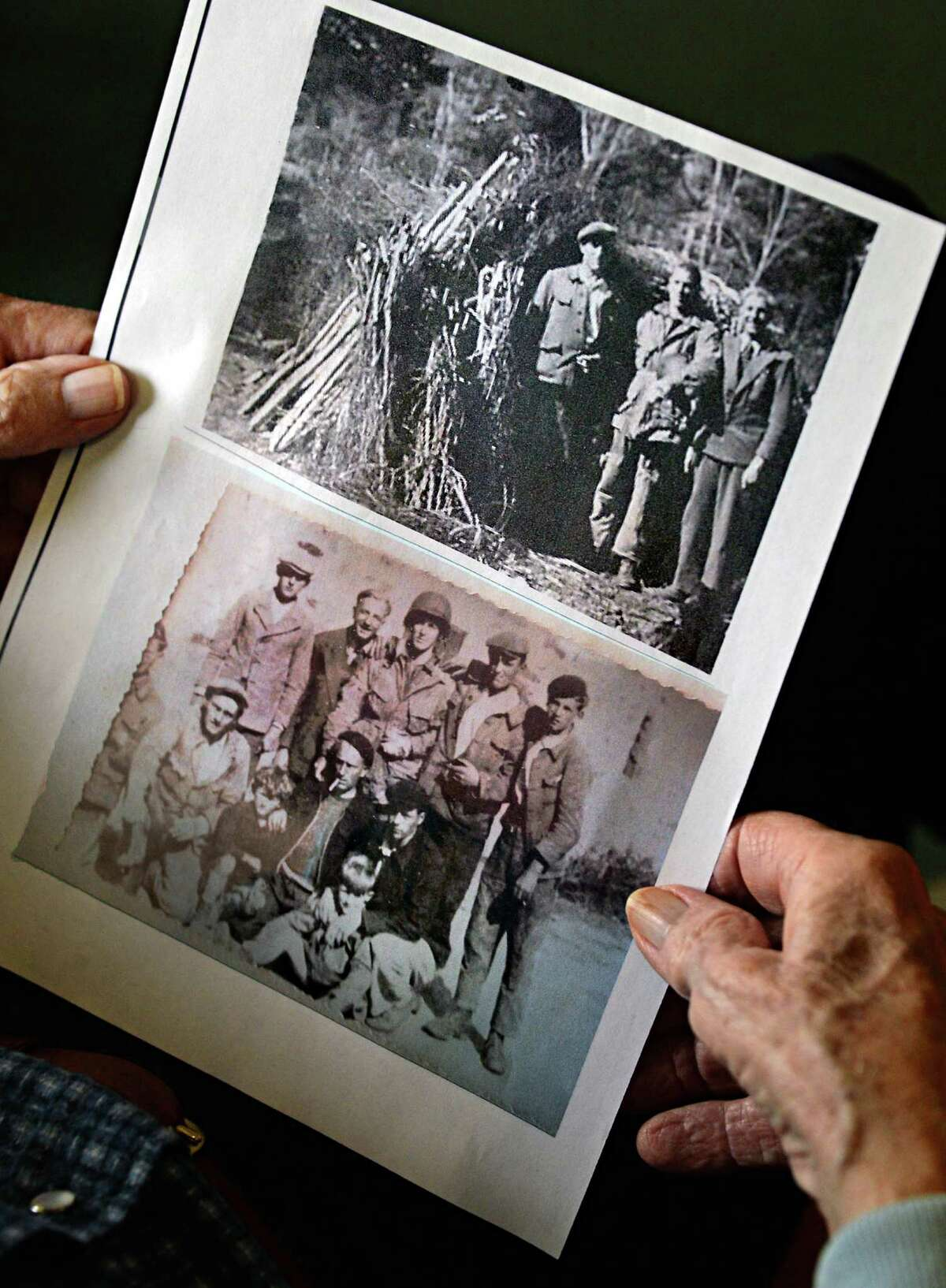 Paul Calhoun Sr., 92, holds photos of French civilians that helped him escape German troops after parachuting into Normandy on D-Day June 6, 1944, during an interview at his Woodlawn Common residence Thursday May 29, 2014, in Saratoga Springs, NY. (John Carl D'Annibale / Times Union