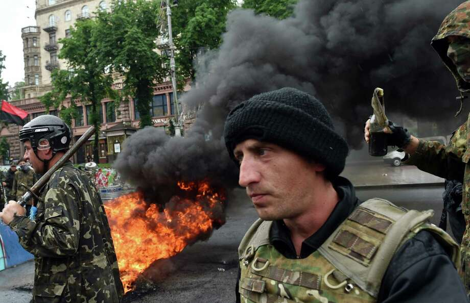 Protesters from Kiev's Independence Square hold a metal bar and a petrol bomb as they burn tires to protect their barricades from being dismantled. Photo: Sergei Supinsky / Getty Images / AFP