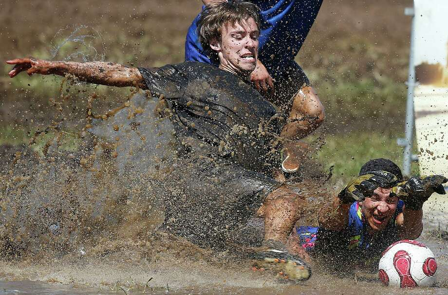 Players  challenge for the ball during the German Mud Soccer  Championships in Rieste, Germany, Saturday, May 31, 2014. Some 1,000 participants from all over Germany compete in three categories, men, women and mixed for the German Championship titles. Photo: Frank Augstein, Associated Press / AP