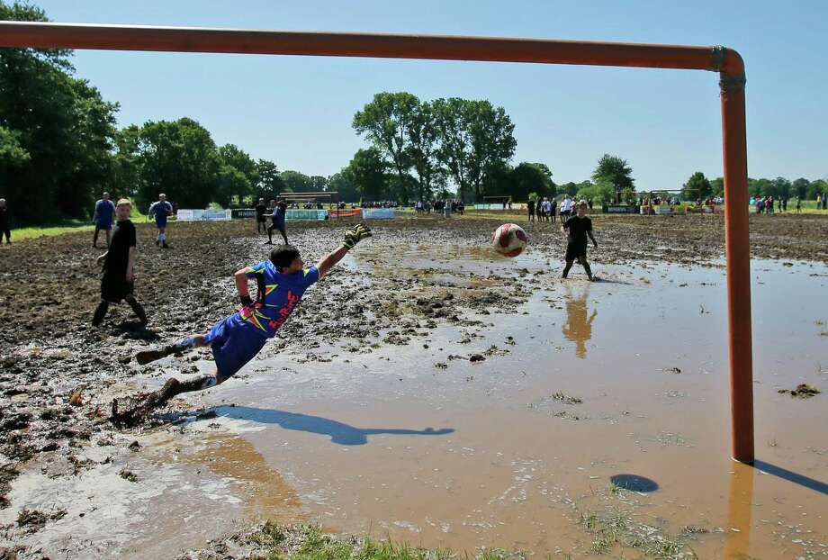 A goalkeeper jumps for the ball during the German Mud Soccer  Championships in Rieste, Germany, Saturday, May 31, 2014. Some 1,000 participants from all over Germany compete  in three categories, men, women and mixed for the German Championship titles. Photo: Frank Augstein, Associated Press / AP