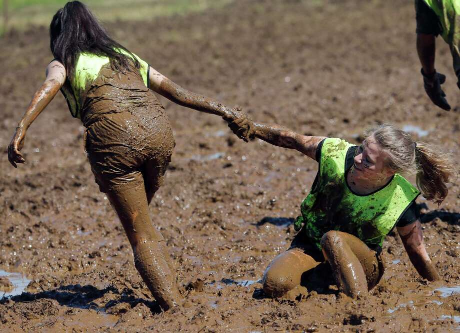 A player helps a teammate out of the mud during the German  Mud Soccer Championships in Rieste, Germany, Saturday, May 31, 2014. Some 1,000 participants from all over Germany compete  in three categories, men, women and mixed for the German Championship titles. Photo: Frank Augstein, Associated Press / AP