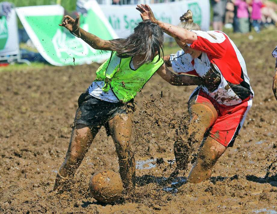 Players challenge  for the ball during the German Mud Soccer Championships in Rieste, Germany, Saturday, May 31, 2014. Some 1,000 participants from all over Germany compete in three categories, men, women and mixed for the German Championships. Photo: Frank Augstein, Associated Press / AP