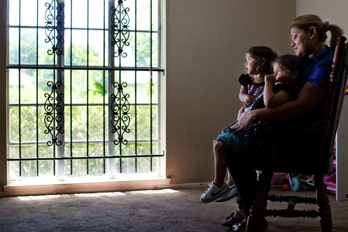 """Maria Cortes, with daughters Denisse Brisuela, left, and Keylin Brisuela, wonders if her husband's homicide was ignored because he wasn't a citizen and because her English isn't good. """"That's the first thing you begin to think, because you're ... not from here."""""""