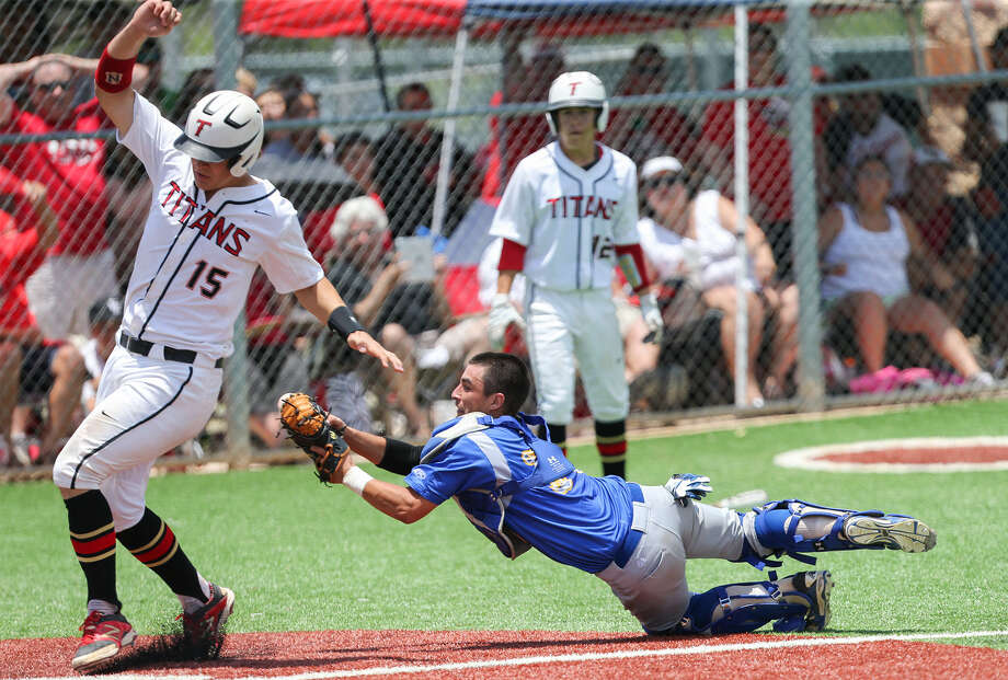 Clemens catcher Brandon Valdez (right) begins to lose the ball after tagging Victoria East's Cole Urban in the fifth inning of Game 3 of the Region IV-4A series at San Marcos High School on Saturday. The Titans beat the Buffaloes 5-1 to advance to state. Photo: Photos By Marvin Pfeiffer / San Antonio Express-News / Express-News 2014