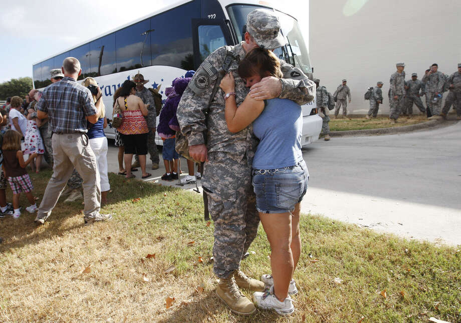 Spc. Daniel Mills hugs his wife upon his return from Iraq. Now some soldiers who put their lives on the line face job loss. Photo: JERRY LARA, San Antonio Express-News / glara@express-news.net