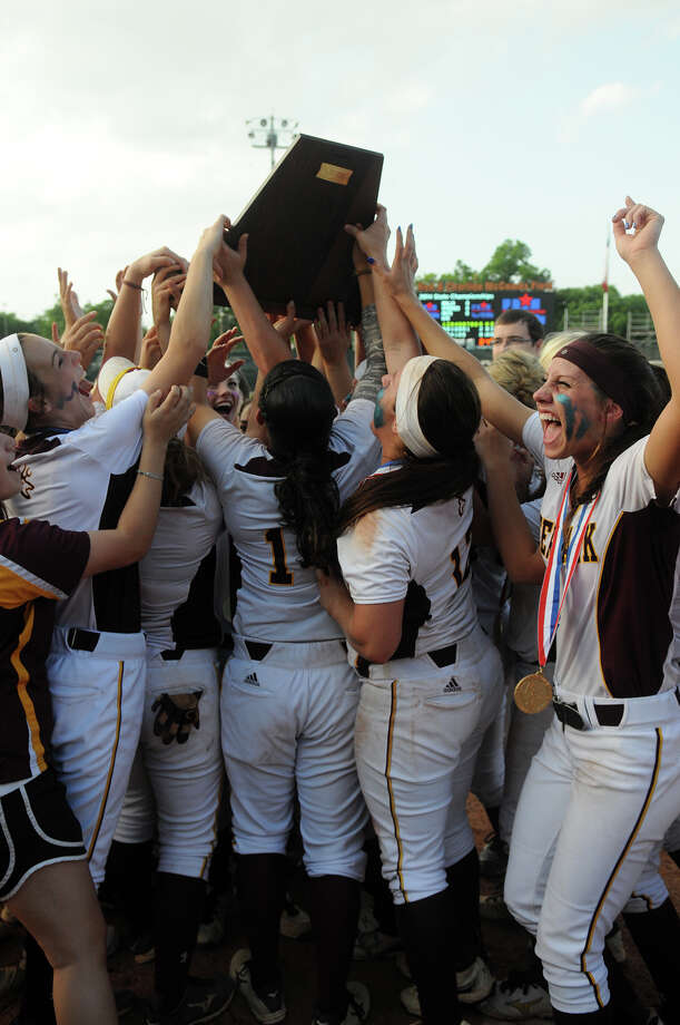 All that was left to do for Deer Park's Devann Hebert, right, and her teammates was to hoist their trophy after defeating The Woodlands in the 5A softball title game. Photo: Jerry Baker, Freelance