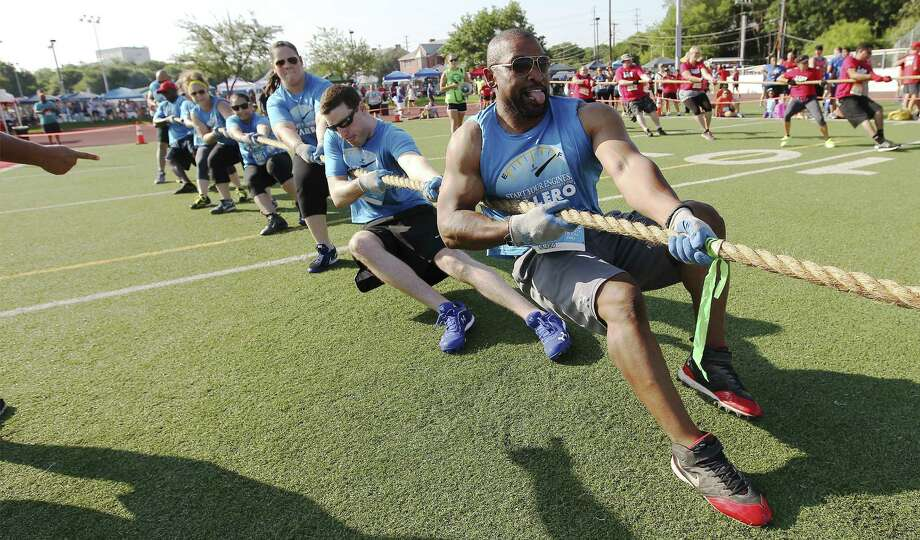 Valero's Lamar Sales (front) leads fellow employees in the tug of war at the San Antonio Sports Corporate Cup at the University of the Incarnate Word. The third annual event brought together 71 teams and about 5,000 people from area companies. Photo: Kin Man Hui / San Antonio Express-News / ©2014 San Antonio Express-News