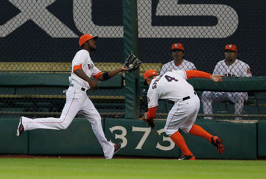 Astros center fielder Dexter Fowler, left, runs down and makes the catch on a long sacrifice fly by the Orioles' Nelson Cruz in the first inning Saturday as right fielder George Springer tries to get out of Fowler's way. Photo: Karen Warren, Staff / © 2014 Houston Chronicle