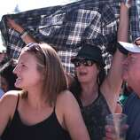 Jasmin Noland, left, and John Noland, right, are shaded by Zorina Noland during Third Eye Blind's set at the 2014 Bottlerock Napa Valley music, food and wine festival on Saturday, May 31, 2014 in Napa, Calif.