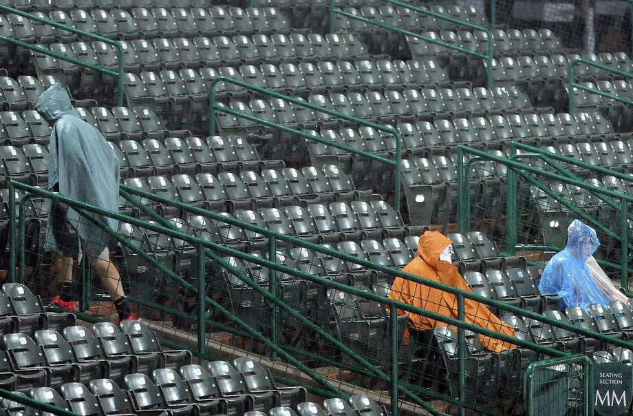 A spectator walks up the stands as other spectators wait during a rain delay before a Houston NCAA baseball regional game between Rice and Texas, Saturday, May 31, 2014, at Reckling Park in Houston. Photo: Eric Christian Smith, For The Chronicle