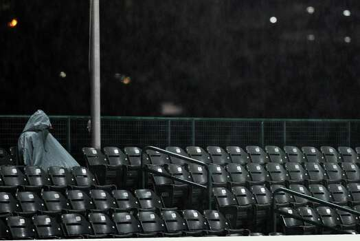 A spectator waits in the stands in the rain during a rain delay before Houston NCAA baseball regional game between Rice and Texas, Saturday, May 31, 2014, at Reckling Park in Houston. Photo: Eric Christian Smith, For The Chronicle