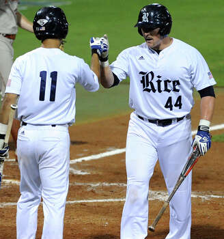 Rice's Skyler Ewing fist bumps Ford Stainback after Ewing scored the Owls' first run of the game during the second inning of a Houston NCAA baseball regional game against Teaxs, Saturday, May 31, 2014, at Reckling Park in Houston. Photo: Eric Christian Smith, For The Chronicle