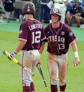 Texas A&M's Krey Bratsen (13) smiles after scoring a run as teammate Cole Lankford looks on during the eighth inning of a Houston NCAA baseball regional game against George Mason, Saturday, May 31, 2014, at Reckling Park in Houston. Photo: Eric Christian Smith, For The Chronicle