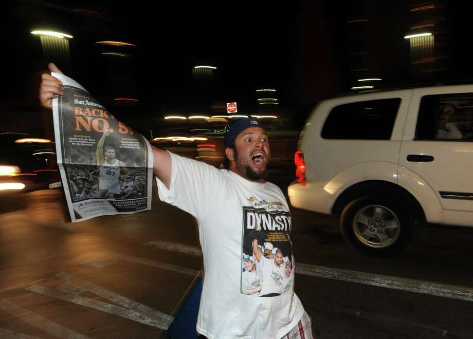 A man distributes a Spurs newspaper section after the teams' victory over Oklahoma City in the NBA Western Conference finals on Saturday, May 31, 2014. Photo: Billy Calzada, 	Billy Calzada/Express-News / © 2014 San Antonio Express-News
