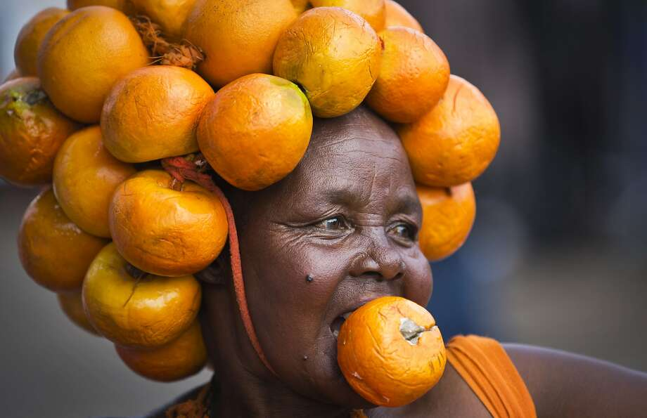 Fruity fashion: A supporter of Kenyan opposition leader Raila Odinga's Orange Democratic Movement dons a headdress of oranges as she attends a rally in Nairobi welcoming Odinga back to the country. Tens of thousands greeted Odinga, who narrowly lost the last election to current President Uhuru Kenyatta and was returning following a three-month sabbatical in the United States. Photo: Ben Curtis, Associated Press