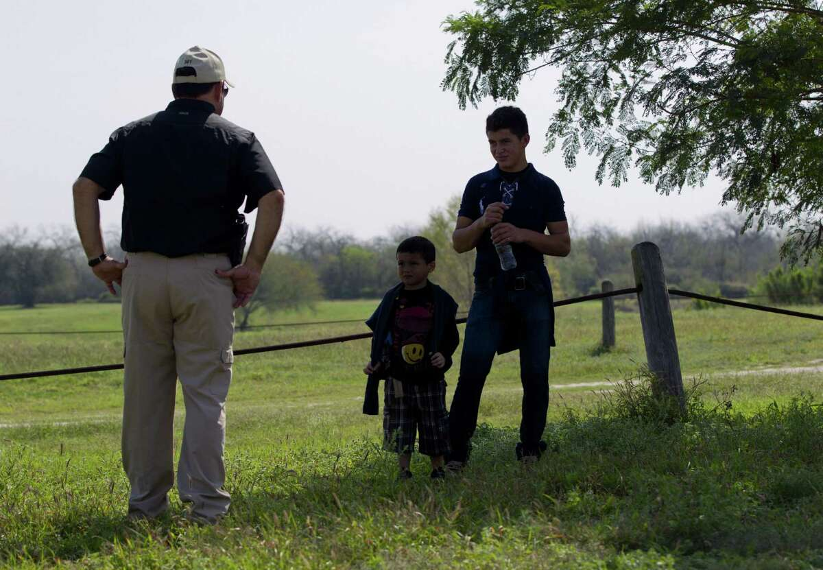 Waiting for the Border Patrol, Hidalgo County Precinct 3 Constable Lazaro Gallardo, Jr., talks to a 4-year-old and his 17-year-old uncle from Honduras, who approached Gallardo in Anzaldulas Park after crossing the Rio Grande from Mexico.