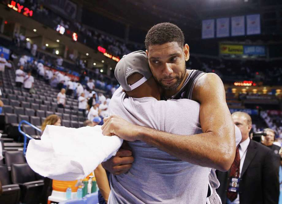 Spurs forward Tim Duncan, right, shares a moment with teammate Patty Mills after San Antonio finished off a 112-107 overtime win over the Thunder to advance to the NBA Finals for the second straight season. Photo: Ronald Martinez, Staff / 2014 Getty Images