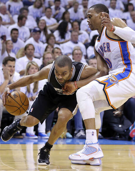 Tony Parker tries to maneuver past Russell Westbrook during the first half. Parker, who was playing on a sprained ankle, finished with eight points before sitting out the second half. Photo: Edward A. Ornelas / San Antonio Express-News / © 2014 San Antonio Express-News