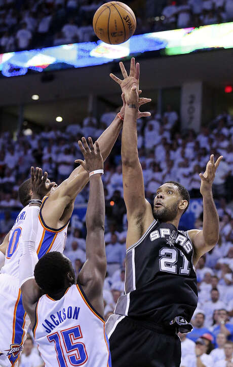 Spurs forward Tim Duncan, who finished with 19 points and 15 rebounds, shoots over Thunder guards Russell Westbrook (left) and Reggie Jackson during overtime of Saturday night's game. Photo: Edward A. Ornelas / San Antonio Express-News / © 2014 San Antonio Express-News