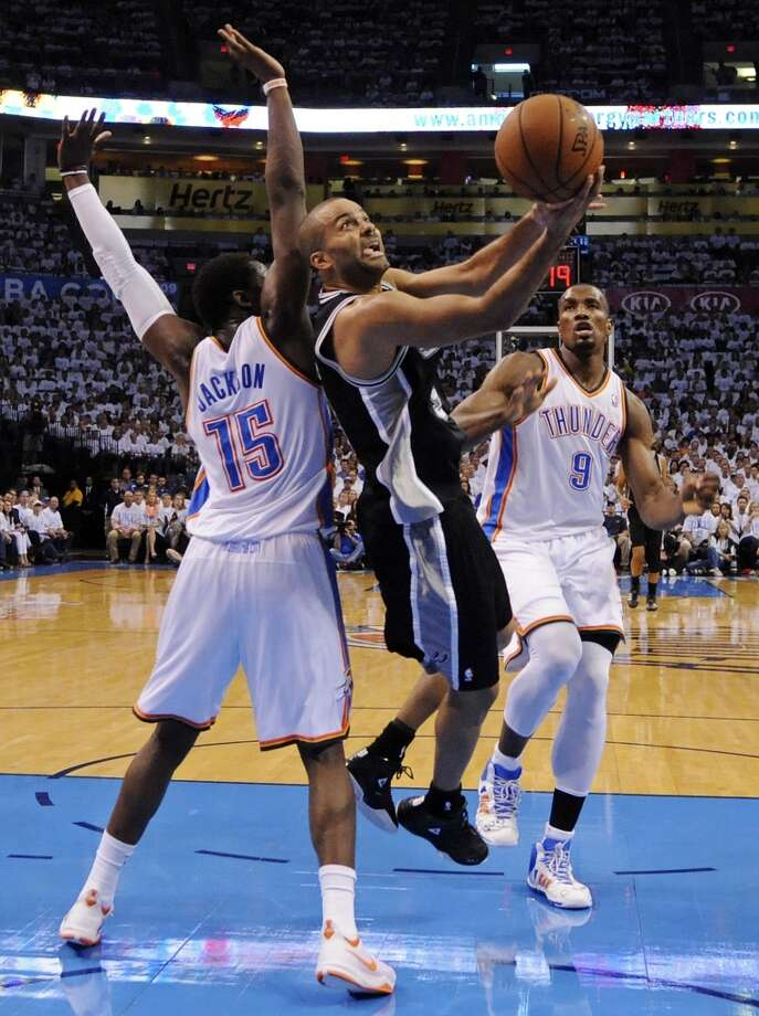 San Antonio Spurs' Tony Parker shoots between Oklahoma City Thunder's Reggie Jackson and Serge Ibaka during first half action in Game 6 of the Western Conference finals Saturday May 31, 2014 at Chesapeake Energy Arena in Oklahoma City, OK. Photo: Edward A. Ornelas, San Antonio Express-News
