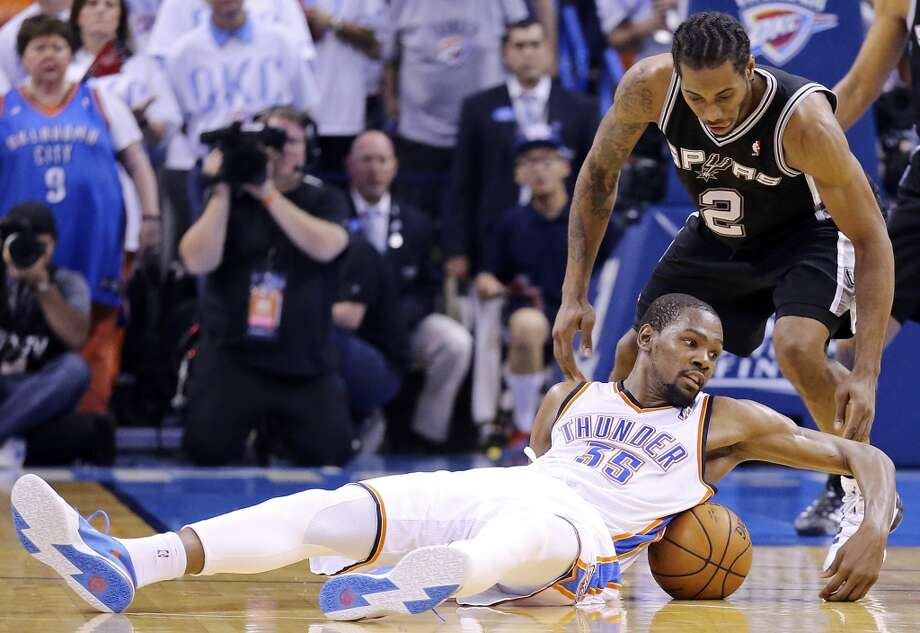 Oklahoma City Thunder's Kevin Durant and San Antonio Spurs' Kawhi Leonard chase after a loose ball during second half action in Game 6 of the Western Conference finals Saturday May 31, 2014 at Chesapeake Energy Arena in Oklahoma City, OK. The Spurs won 112-107 and advance to the NBA Finals to play the Miami Heat. Photo: Edward A. Ornelas, San Antonio Express-News