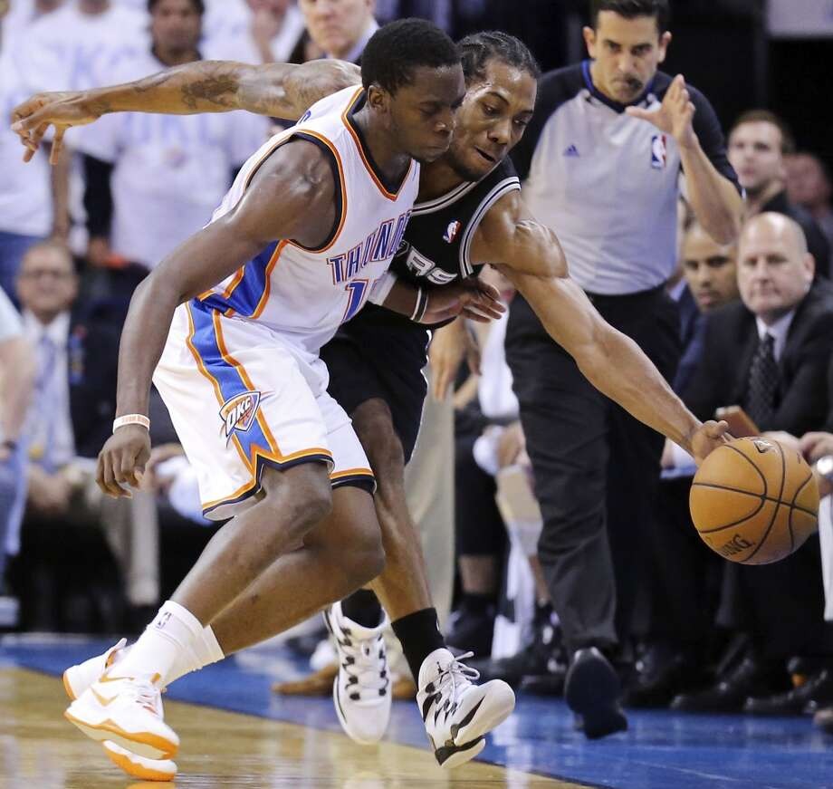 Oklahoma City Thunder's Reggie Jackson and San Antonio Spurs' Kawhi Leonard chase after a loose ball during first half action in Game 6 of the Western Conference finals Saturday May 31, 2014 at Chesapeake Energy Arena in Oklahoma City, OK. Photo: Edward A. Ornelas, San Antonio Express-News