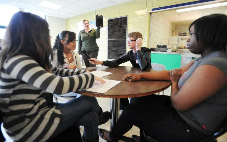 Brendan George, 13, listens to Michelle Rodriguez, 13, as Sabrina Petrafesa, 13, and Codi-ann Montaque, 13,  a group of eighth grade students at Rippowam Middle School, present a skit in the cafeteria to demonstrate the peer mediation program they've set up at the school in Stamford, Conn. on Friday, Feb. 5, 2010. Photo: Kathleen O'Rourke / Stamford Advocate