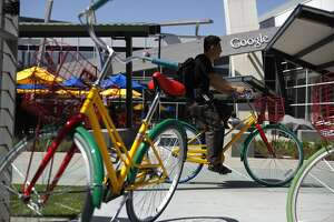 A person rides a Google bike past a building on the Googleplex Campus in Mountain View, CA, Thursday May 29, 2014.