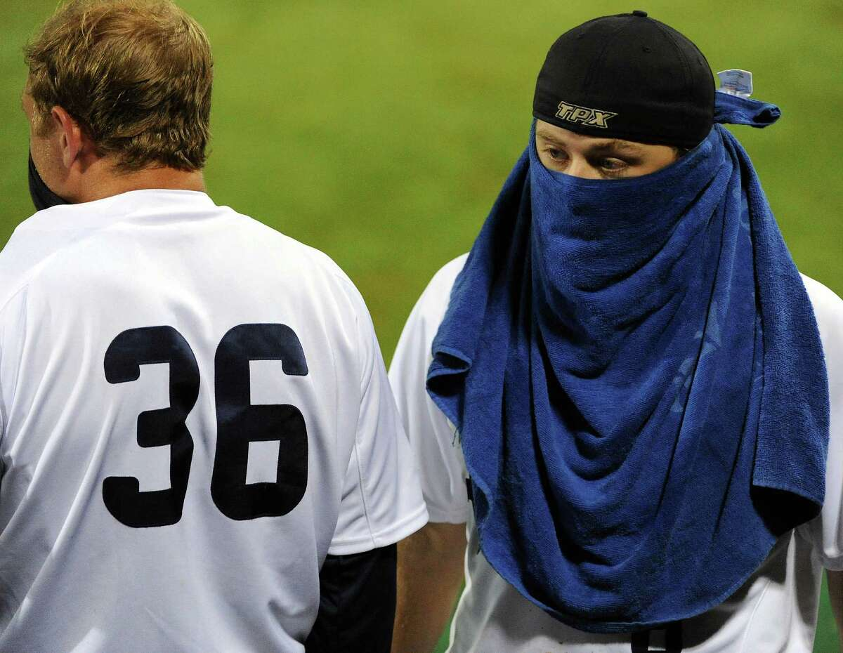 Rice's John Williamson, right, dresses up like a bandit during the Owls' turn-at-bat in the eleventh inning of a Houston NCAA baseball regional game against Texas, Saturday, May 31, 2014, at Reckling Park in Houston.