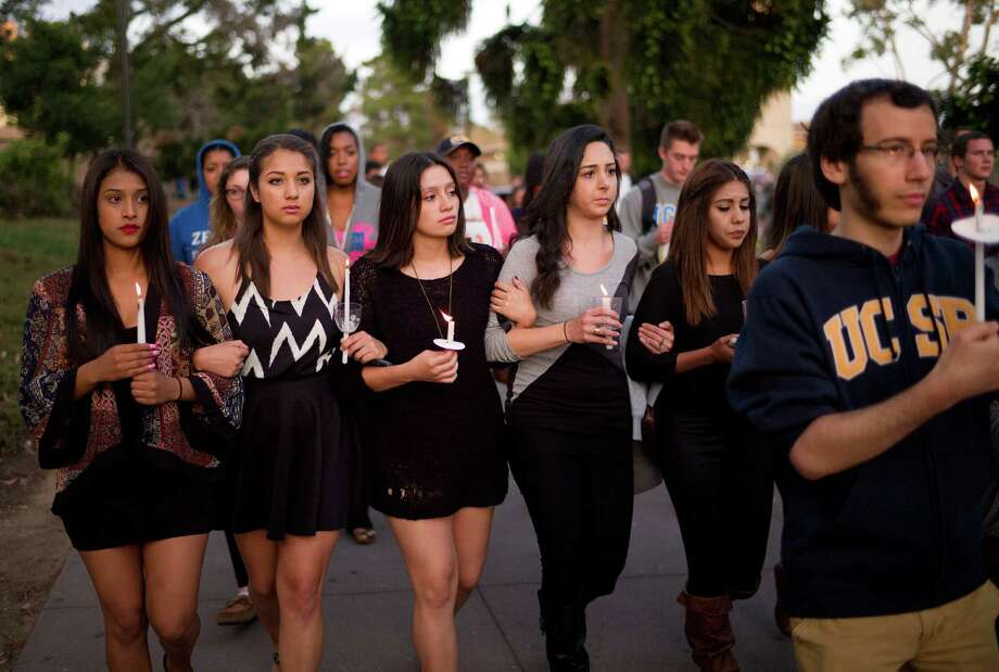 """Students march at the University of California, Santa Barbara during a candlelight vigil held to honor the six victims of a mass killing in Isla Vista, Calif. The parents of killer Elliot Rodgers had gone to police three weeks before his rampage. Deputies """"determined he did not meet the criteria for a temporary hold,"""" said Santa Barbara Sheriff Bill Brown. An initiative campaign for Extreme Risk Protection Orders has just been launched in Washington. Photo: Jae C. Hong, AP  / AP"""