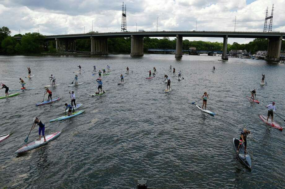 Stand up paddleboarders navigate the Saugatuck River in the 3-mile open in Saturday's 2014 Soundsurfer Waterman's Challenge. Photo: Jarret Liotta / Westport News