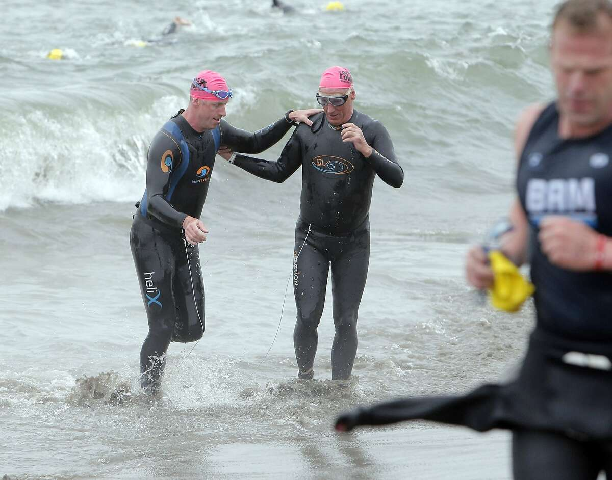 Brian Cowie, who is legally blind, right, and Meyrick Jones, who is a below the knee amputee, left, emerge from the water at Marina Green Beach tethered together during the 34th annual Escape from Alcatraz Triathlon in San Francisco, Calif., on Sunday, June 1, 2014.