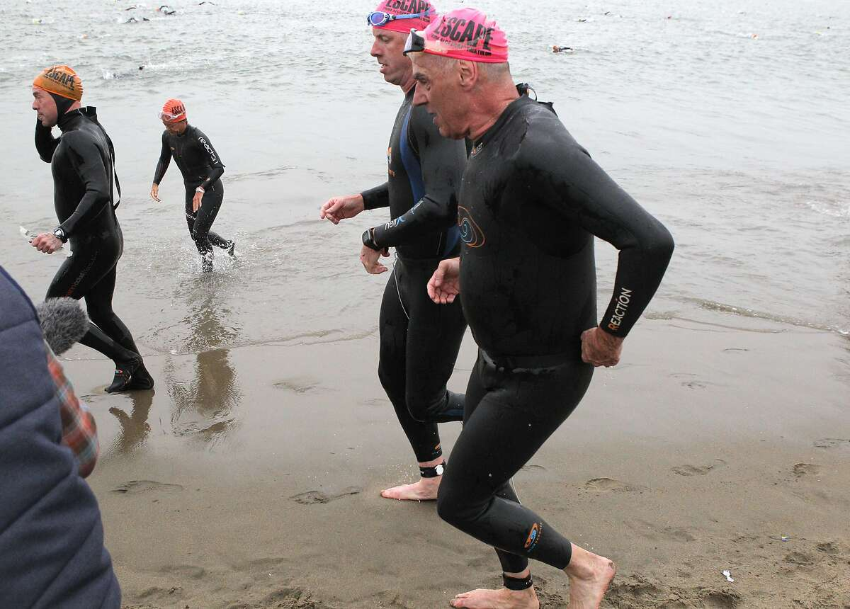 Brian Cowie, who is legally blind, front, and Meyrick Jones, who is a below the knee amputee, rear, emerge from the water at Marina Green Beach tethered together during the 34th annual Escape from Alcatraz Triathlon in San Francisco, Calif., on Sunday, June 1, 2014.