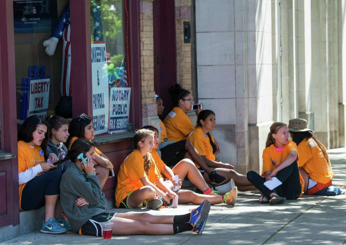 Volunteers wait in the shade after the start of the 19th annual