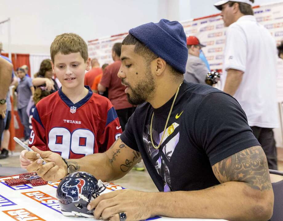 The Tristar 28th Annual Summer Collectors Show is being held this weekend at NRG (Reliant) Center, Hall E. Thousands attend to buy and sell memorabilia and get autographs and photographs with sports stars. ID: Arian Foster spends a moment talking with 8-year-old fan Sam Ullrich of Conroe. Sunday  June 1, 2014 Photo: Craig Hartley, For The Chronicle / Copyright: Craig H. Hartley