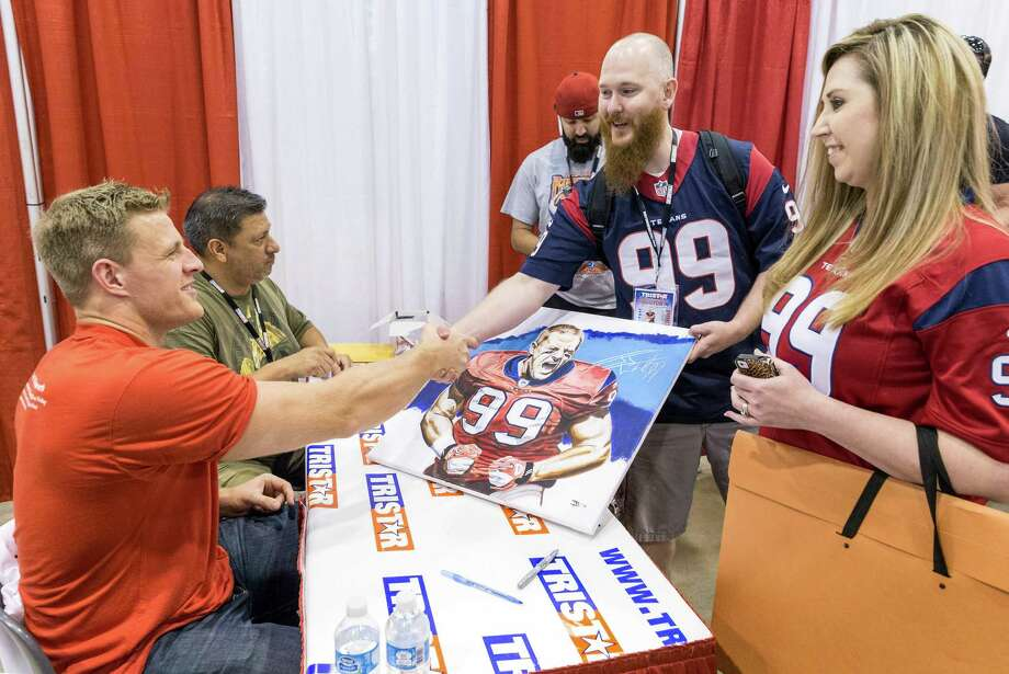 The Tristar 28th Annual Summer Collectors Show is being held this weekend at NRG (Reliant) Center, Hall E. Thousands attend to buy and sell memorabilia and get autographs and photographs with sports stars. ID: Jason March and Christina March of Houston shake hands with J.J. Watts after getting their painting signed. Sunday  June 1, 2014 Photo: Craig Hartley, For The Chronicle / Copyright: Craig H. Hartley