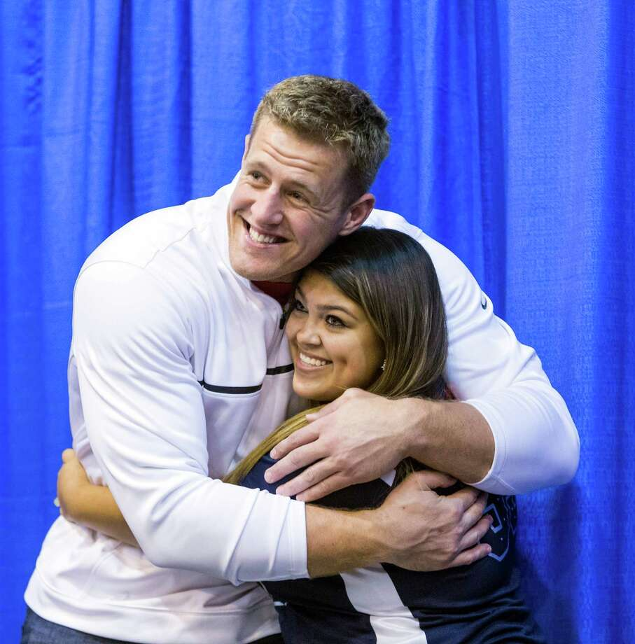 The Tristar 28th Annual Summer Collectors Show is being held this weekend at NRG (Reliant) Center, Hall E. Thousands attend to buy and sell memorabilia and get autographs and photographs with sports stars. ID: Marissa Vargas of Houston gets a big hug, then is overcome with embarrassment, as she poses for pictures with J.J. Watt. Sunday  June 1, 2014 Photo: Craig Hartley, For The Chronicle / Copyright: Craig H. Hartley