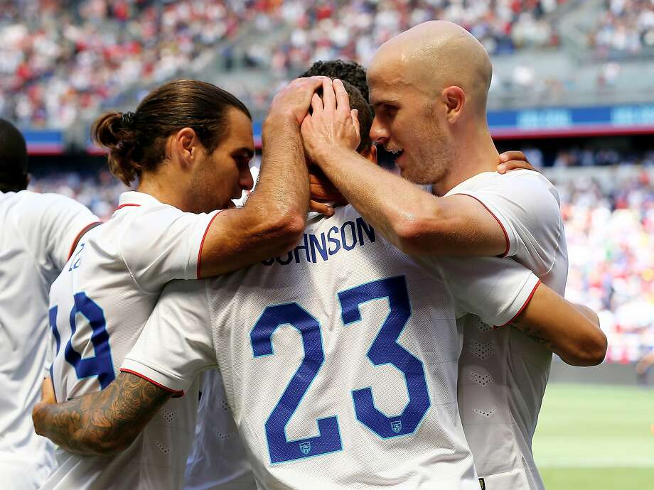 Graham Zusi (left) and Michael Bradley (right) congratulate Fabian Johnson after his goal. Photo: Elsa, Getty Images