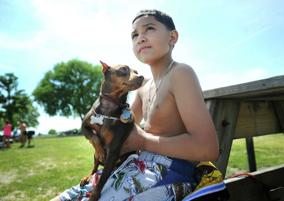 "Nathan Diaz, 10, of Bridgeport, hangs out with his dog ""Kandy"" in a picnic area just off the sand at Seaside Park in Bridgeport, Conn. on Sunday, June 1, 2014. The Bridgeport City Council is considering an ordinance banning dogs from all beach parks in the city. Photo: Brian A. Pounds / Connecticut Post"