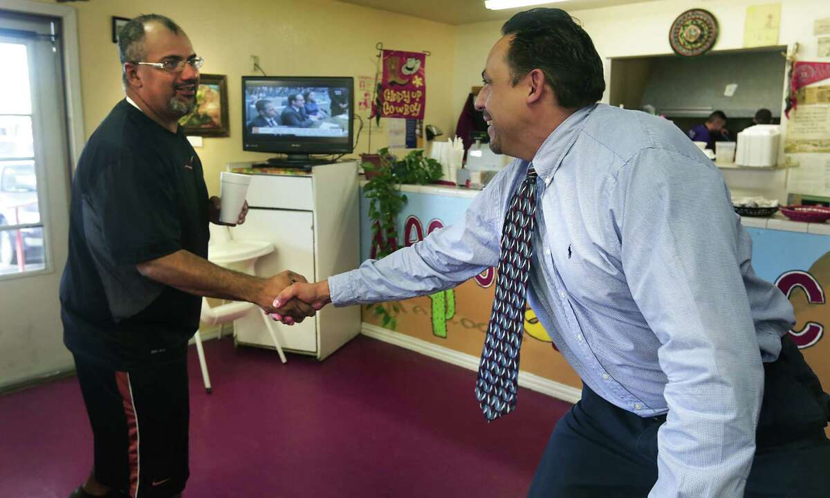 Eleazar Cano, right, of Alpine, TX, running for Brewster County Judge, greets William Torres, whom he has known all his life, in a local restaurant. Thursday, May 15, 2014.