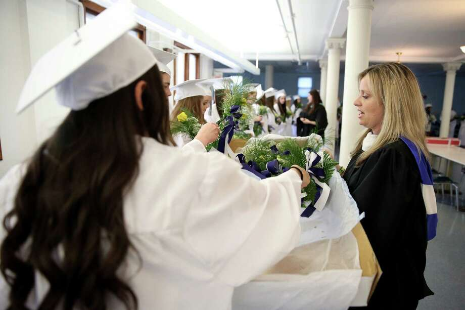 Lauralton Hall High School history teacher Courtney Dwyer hands out roses to students at staging area for commencement exercises at the school in Milford, Conn. on Sunday June 1, 2014. Photo: Mike Ross / Mike Ross Connecticut Post freelance - @www.mikerossphoto.com
