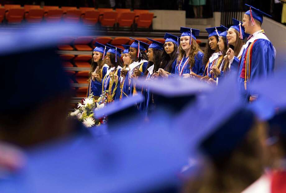 Oak Ridge High School graduates stand to sing the alma mater at the end of commencement at Sam Houston State University Saturday, May 31, 2014, in Huntsville. Photo: Brett Coomer, Houston Chronicle / © 2014 Houston Chronicle