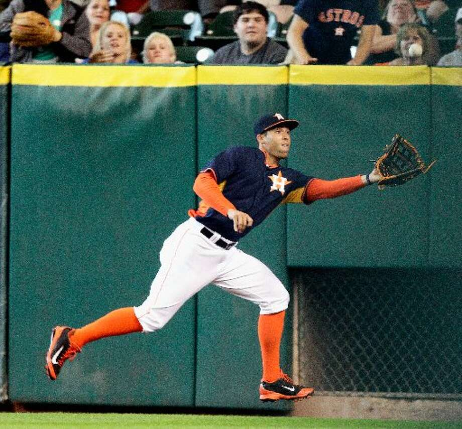George Springer makes a running catch in the corner on a line drive by Nick Hundley in the sixth inning. Photo: Bob Levey, Getty Images