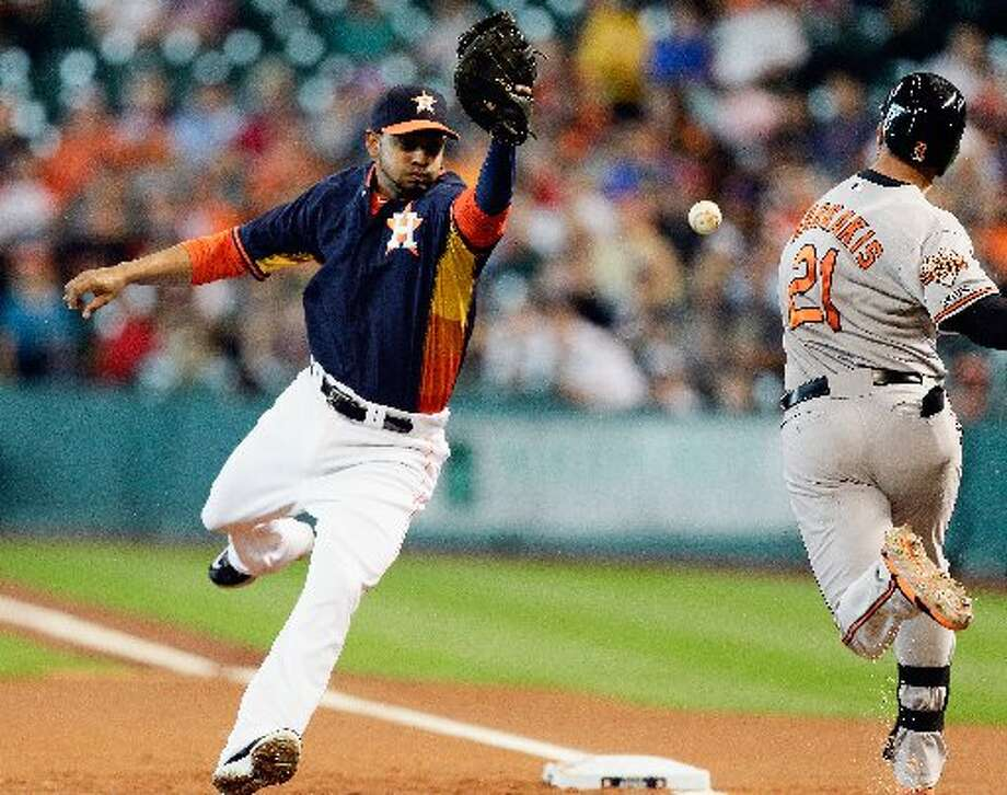 Nick Markakis is hit by a throw as Jesus Guzman can't catch the ball in the first inning. Photo: Bob Levey, Getty Images